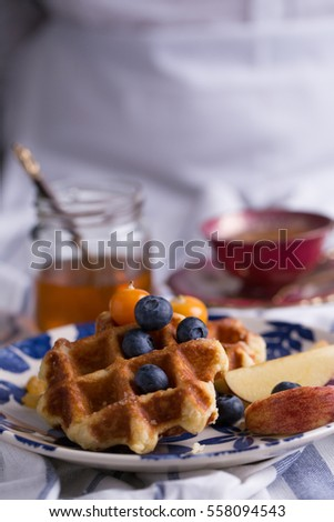 Blueberry apple waffle with honey set on a dish decorated with fresh blueberry, apple, tea pot.