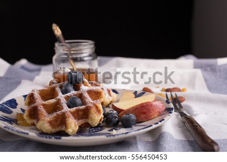 Blueberry apple waffle with honey set on a dish decorated with fresh blueberry, apple, tea pot with copy space.