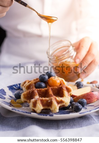 Blueberry apple waffle with honey set on a dish with a chef's hand holding spoon for a jar of honey ready to serve.