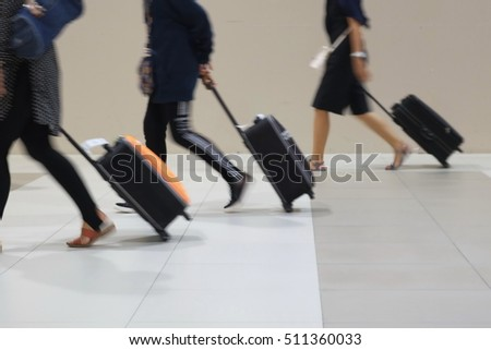 Blur and movement of people dragging suitcases in a hurry.
