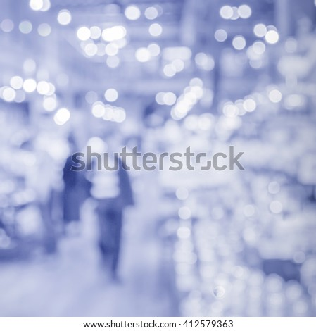 blur customer shopping in supermarket with light bokeh