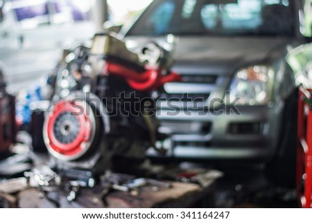 Blurred background : Car technician repairing the car in garage.