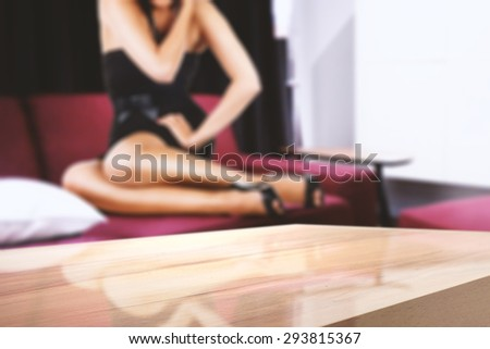 blurred background of woman on sofa and free space for you on board and desk