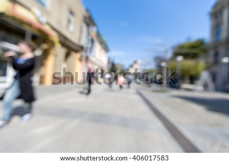 blurred background. people walking on a city street. street on a spring day. business street