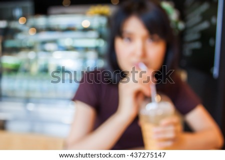 Blurred background. woman sitting at coffee shop with ice coffee on wooden table.