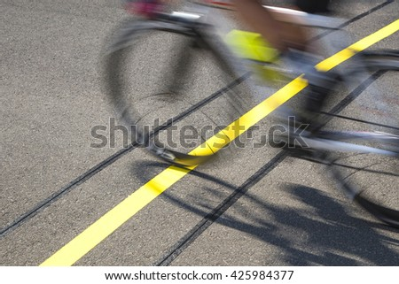 Blurred cyclist, due to speed, reaching the finishing line on a race. The action focus on the goal line