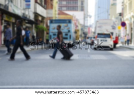 blurred image background, group of pedestrian crossing the road at sunny day.