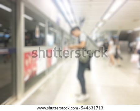 Blurred passenger in the subway station and use the phone. Artificial lighting techniques