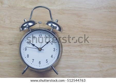 Blurry Black Coffee Open Notebook With Old Fashioned Alarm Clock On Wood  Table. With