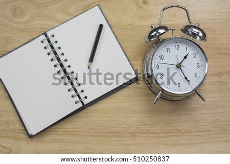 Blurry Black Coffee Open Notebook With Pencil And Old Fashioned Alarm Clock  On Wood Table