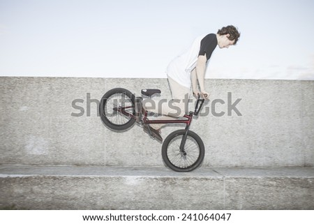 Bmx rider performing a nose manual on concrete block