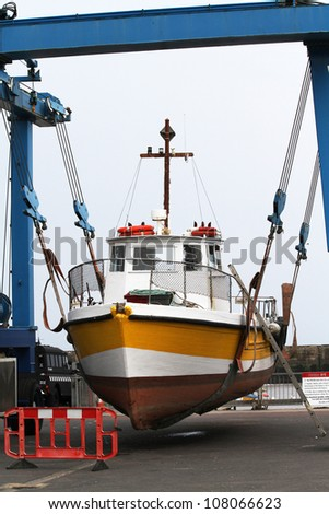 Port crane boats on pier stock photo 128017385 shutterstock for Outboard motor lifting strap