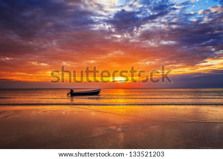 Boat on the beach at sunset in tide time.