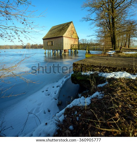 boathouse with a frozen lake at the Plothener Seenplatte