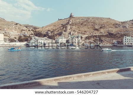 Boats in the Balaklava Bay and the ancient ruins of the Cembalo fortress on top of a mountain in Balaklava, outskirts of Sevastopol, Crimea.