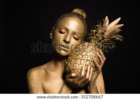 body-paint. gold bod-yart. beautiful sexy girl with fruit. golden makeup
