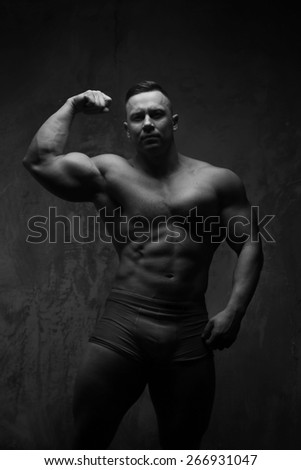 Bodybuilder shows his muscle. Isolated on grey backround