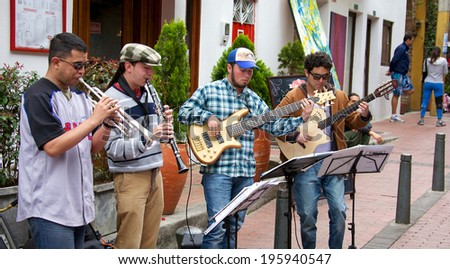 BOGOTA, COLOMBIA - APRIL 06, 2014: Unidentified musical quartet playing for money in the streets of Usaquen in Bogota Colombia. Usaquen was declared a national monument in 1987.