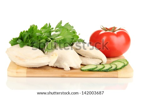 Boiled chicken breast on wooden cutting board with vegetables isolated on white