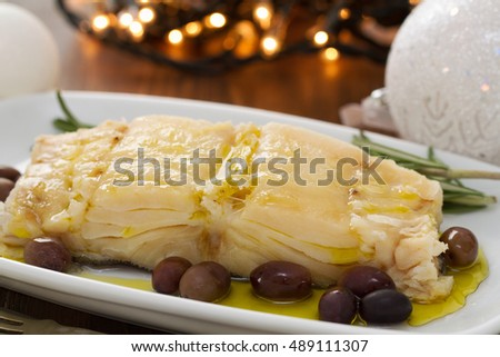 boiled cod fish with oil and olives on white dish