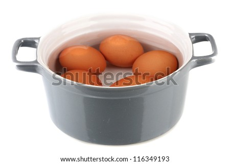 Boiled eggs in saucepan isolated on white