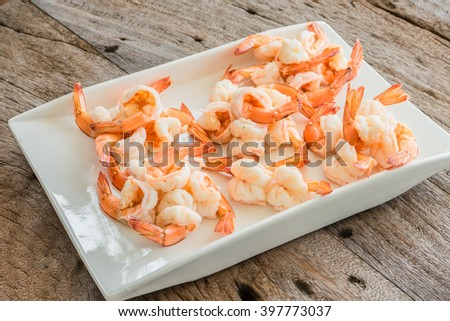 boiled shrimp on a white plate on a wooden background