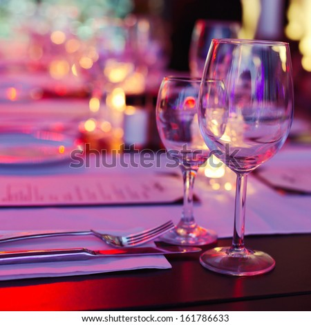 Bokeh background of table in restaurant. Selective focus on reflection in the glass.