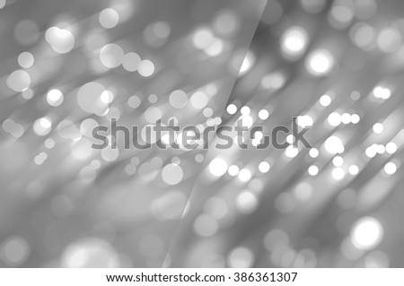 Bokeh light, shimmering blur spot lights on silver abstract background.