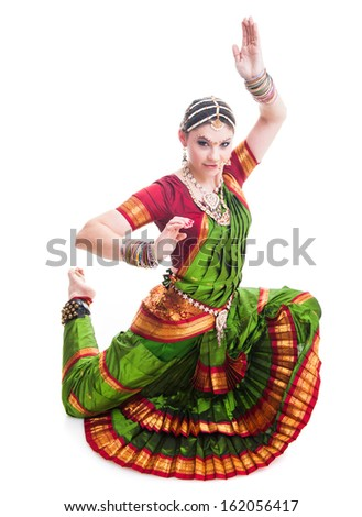 Bollywood dancer in green and orange folded dress posing as cobra