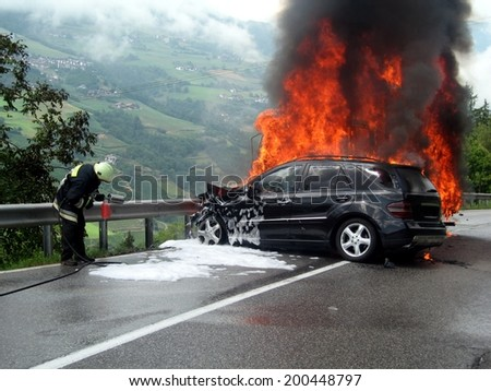 BOLZANO,  ITALY -  JULY 19, 2013: car and small truck crashed and catch fire on the road near Bolzano on July 19, 2013 with intervention of one firefighter