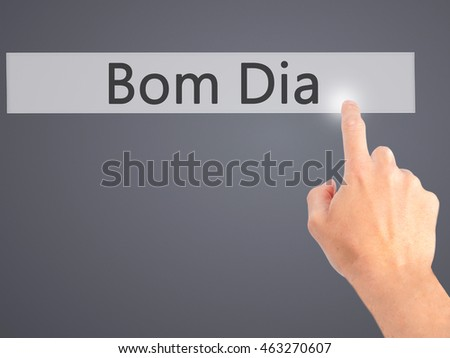Bom Dia (In portuguese - Good Morning) - Hand pressing a button on blurred background concept . Business, technology, internet concept. Stock Photo