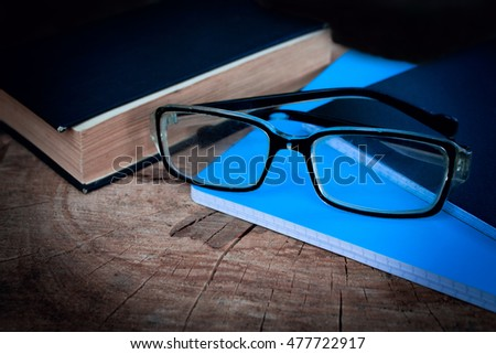 Book and glasses in the wooden table