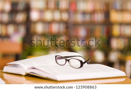 book and glasses on table in library
