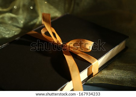 Book wrapped with color ribbon, on wooden background