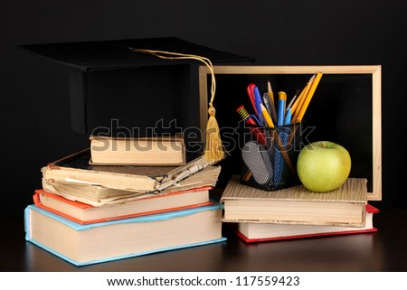 Books and magister cap against school board on wooden table on black background