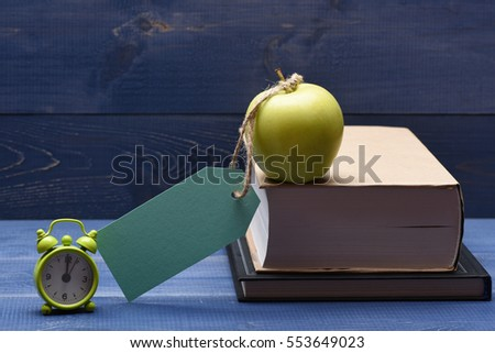 Books, fresh green apple with turquoise tag, string and alarm clock on blue vintage wooden background, education concept, copy space