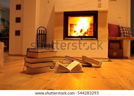 books on wooden floor in front of fireplace