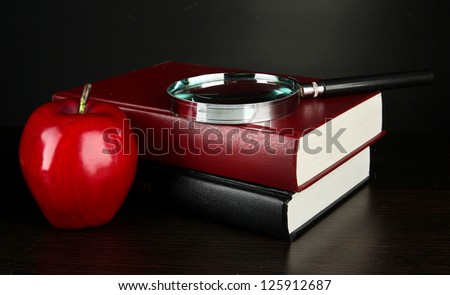 books with magnifying glass on table on black background