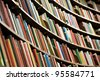 Bookshelf in library with many books. Shallow dof. - stock photo