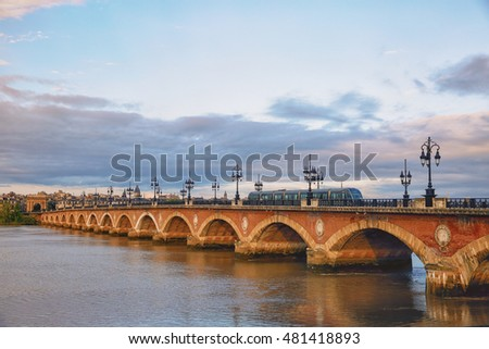 BORDEAUX, FRANCE - July 31, 2016: Tram passing on the famous Pont de Pierre stone bridge in the morning