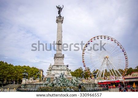BORDEAUX, FRANCE, OCTOBER 24, 2015 - The Monument des Girondins with statue of the angel of liberty at the top, and big wheel at attraction fair