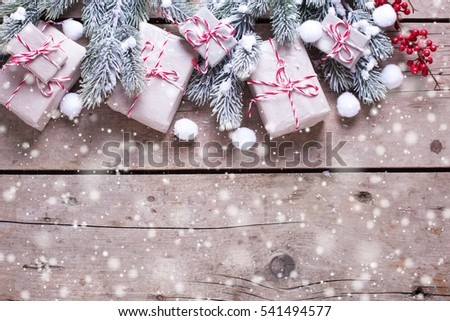 Border from wrapped christmas presents, fur tree branches, red berries on aged wooden background. Selective focus. Place for text. Drawn snow.