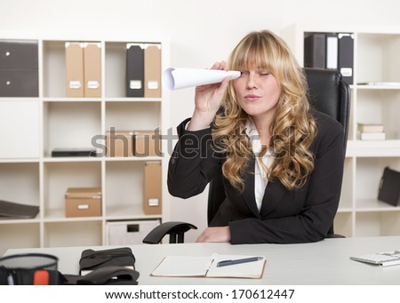 Bored young businesswoman sitting at her desk in the office playing with a paper telescope made from a rolled sheet of paper holding it to her eye