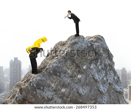 Boss using megaphone commanding employee carrying big 3D gold dollar sign on top of mountain peak with urban scene background