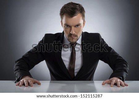 Bossy man. Angry young man in formalwear looking at camera while sitting at the table isolated on grey