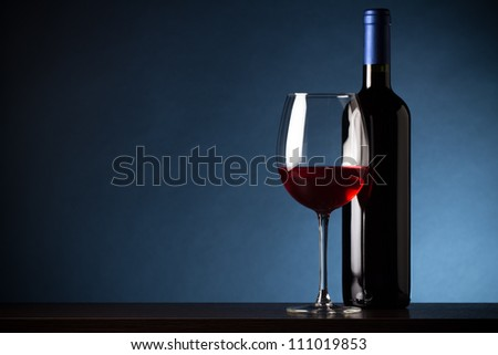 Bottle and glass of red wine on blue background