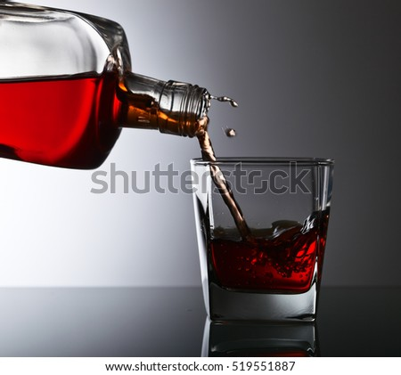 bottle and glass of whiskey on a glass table in bar