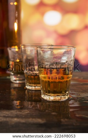 bottle and three glasses of rum whiskey alcohol on wooden table over defocused lights background