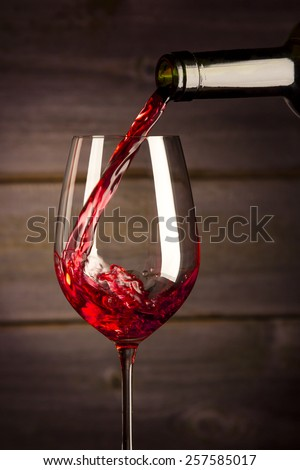 Bottle filling the glass of wine - splash of delicious flavor. on a wooden background.