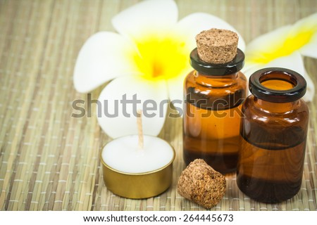 bottle of aroma essential oil with lotus flower and candle on wooden background, spa concept.